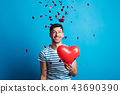 A young man in love holding red heart, confetti falling on him. 43690390