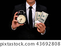 Business concept. Businessman holding a clock on a black backgro 43692808
