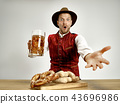 Germany, Bavaria, Upper Bavaria, man with beer dressed in traditional Austrian or Bavarian costume 43696986