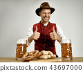 Germany, Bavaria, Upper Bavaria, man with beer dressed in traditional Austrian or Bavarian costume 43697000