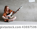 Young red-haired girl with an electric guitar. Rock musician gir 43697506