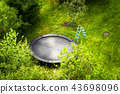 Large trampoline in a garden with a ladder 43698096