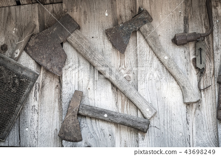 Old axes hanging on a wall 43698249