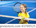 Child playing tennis on indoor court 43700525