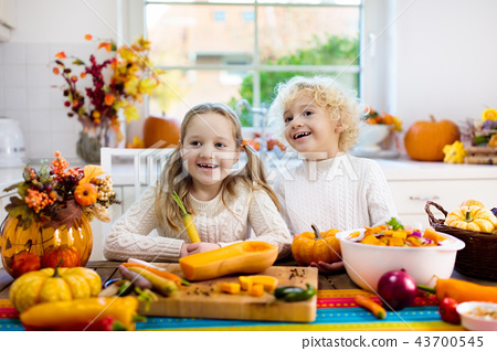 Kids cooking pumpkin soup for Halloween lunch 43700545