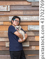 Asian woman hugging dog so cute with wooden wall 43702769
