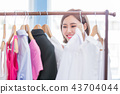 woman choosing clothes in showroom 43704044
