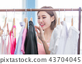 woman choosing clothes in showroom 43704045