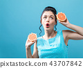 Young woman holding oranges 43707842