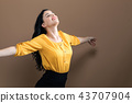 Young woman with her arms outstretched 43707904