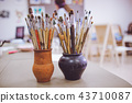 A bunch of art brushes standing in ceramic vases, on the table in the art studio 43710087