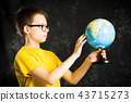 Schoolboy exploring world through a globe 43715273