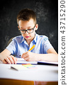 Schoolboy finishing homework at home 43715290