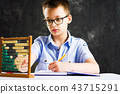 Boy solving math problems at home 43715291