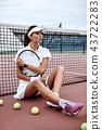 Young beautiful sportswoman with tennis racket sitting at tennis net on tennis court. Sports Fashion 43722283