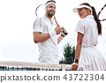 They play like a team. Beautiful young woman and man holding tennis racket and discussing set 43722304
