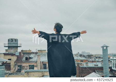 girl in black standing on the edge of the roof 43724925