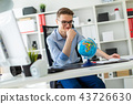 A young man sits in the office at a computer desk and in front of him stands a globe. 43726630