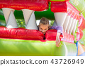 The girl lies in the mouth of the dragon on a soft inflatable trampoline 43726949