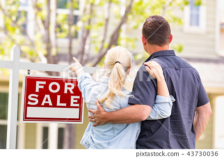 Couple Facing and Pointing to a For Sale Sign 43730036