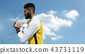 Goalkeeper holding football tight with sky 43731119