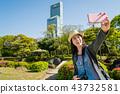 woman taking selfie with skyscraper in garden. 43732581