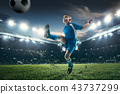Young boy with soccer ball doing flying kick at stadium 43737299