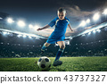 Young boy with soccer ball doing flying kick at stadium 43737327
