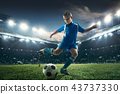 Young boy with soccer ball doing flying kick at stadium 43737330