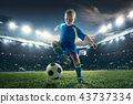 Young boy with soccer ball doing flying kick at stadium 43737334