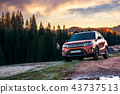 orange 4wd suv parked in mountain at sunrise 43737513
