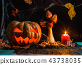 Halloween photo of table with pumpkin, biscuits, dried flowers, burning candle 43738035