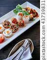 Asian canapes appetizer on white plate, wood table 43739831