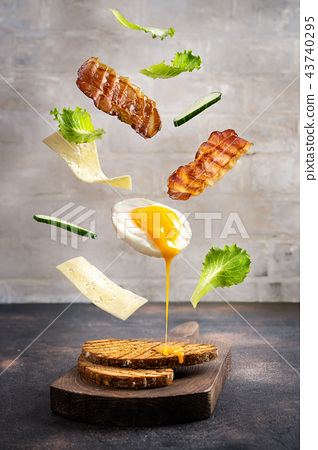 Breakfast sandwich in levitation above cutting board 43740295