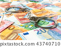Euro banknotes and metal handcuffs 43740710