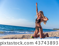 blond woman girl sits in black bikini beach tropic 43743893