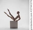 Ballerina. Young graceful female ballet dancer dancing at studio. Beauty of classic ballet. 43744376