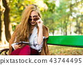 Fashionable woman on a park bench with smart phone 43744495