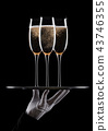 Hand with glove holds tray with champagne glasses 43746355