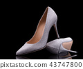 Elegant silver shoes on a black background. 43747800