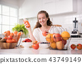 Woman in a kitchen with fruits and juice 43749149