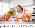 Woman in a kitchen with fruits and juice 43749153
