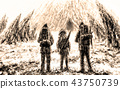 Three men stands at the entrance to the cave. 43750739