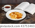 Pancakes on white plate with tea and book 43753463