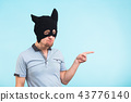 Man wearing black mask pointing on blue background with copy space. Anonymous social masking concept 43776140
