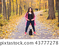 Autumn, pets, people concept - happy plus size woman laughing with the black cat 43777278