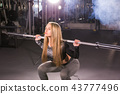 sport, fitness, training and happiness concept - sporty woman with barbell in gym 43777496