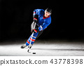 Young hockey player skating on rink in attack 43778398