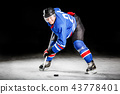Young hockey player skating on rink in attack 43778401