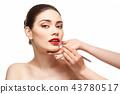 girl applying red lipstick isolated on white 43780517